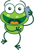 Green frog talking on a smartphone Stock Photography