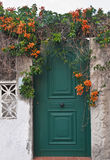 Green front door with orange flowers Stock Images