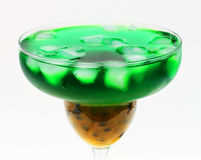 Green fruit cocktail. A succulent passion fruit cocktail, showing the passion fruit nectar has sunk to the bottom of the glass and green alcohol has risen to the royalty free stock image