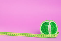 Green fruit with meter on pink Stock Images