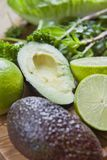 Green fruit and vegetable - wooden board with green food  ingredients: garlic, avocado, lime, mint, cilantro, leek, green chili. Green fruit and vegetable royalty free stock photos