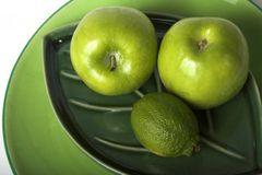 Green fruits on plates. Green fruits stock images
