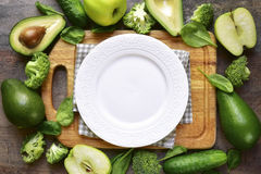 Green fruits and vegetables with cutting board and empty white p Royalty Free Stock Photo