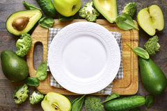 Green fruits and vegetables with cutting board and empty white p Stock Photo