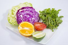 A plate of vegetables and fresh lime and lemon. Green fruits and vegetables are loaded with important vitamins and minerals like vitamin A, vitamin C, potassium Stock Image