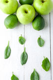 Green fruits on white wooden background. Apple, lime, spinach. Detox. Healthy food. Top view. Copy space. Green fruits on white wooden background. Apple, lime stock photo