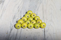 Green fruits on wooden background. The fruits of wild pear stock photos