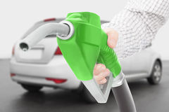 Green fuel pump gun in hand with car on background. Green color fuel pump gun in hand with car on background Stock Photos