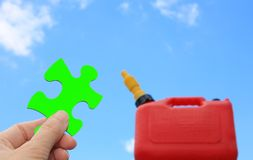 Green fuel solution. Hand holding green puzzle piece towards out of focus gas can against blue sky Stock Image
