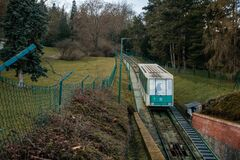 Free Green Funicular Car From Ujezd To Petrin Hill As A Part Of Public Transportation, Park Garden, Benches, Trees And Shades On Sunny Stock Photo - 210926930