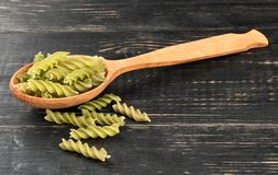 Fusilli pasta in spoon. Green fusilli pasta in spoon on wooden background royalty free stock image