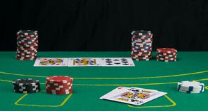 Green gambling table, with betting chips and cards with back black background stock photography