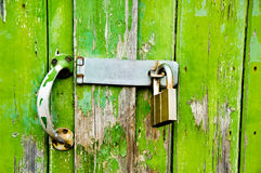 Green Garage Door Lock. A decaying, peeling, grungy green garage door with a lock Royalty Free Stock Photo