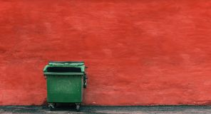 Green garbage container on a red wall background.  stock photo