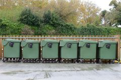 Green garbage containers arranged in a row on the street Royalty Free Stock Images