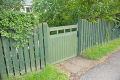 Green garden gate and fence. An image of a wooden garden gate and matching fence coated in green preservative stock photography