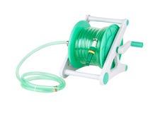 A green garden hose coiled. With spray nozzle stock photography