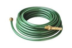 Green garden hose coiled with spray nozzle Royalty Free Stock Photography