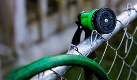 Green garden hose nozzle on a fence near. An over hanging hose royalty free stock photography
