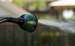 Green garden hose nozzle spraying water. Green garden hose nozzle sprayer being used to water yard stock photo