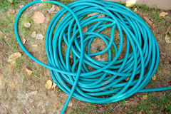 Green garden hose in a roll. Green garden hoses in a roll stock image