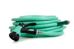 Green garden hose with spray nozzle. A green garden hose with spray nozzle on a white background stock image