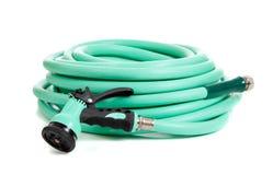 Green garden hose on a white background. A green rubber garden hose with nozzle on a white background stock photos