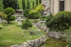 Green garden of japanese design. Artificial creek and bright trees in garden stock image