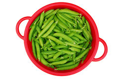 Green garden peas in red colander Royalty Free Stock Photos