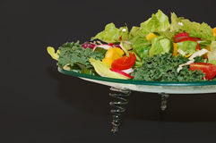 Green garden vegetables on glass plate. With black background Royalty Free Stock Images