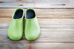 Green Gardening Shoes on Wood Surface Royalty Free Stock Images
