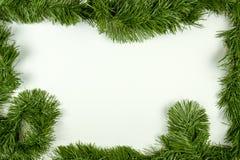 Green garland frame on white. Green garland border framing white copy space for Christmas Stock Image