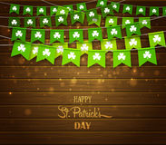 Green garlands of flags with clovers on wood background. Irish holiday Saint Patrick`s Day. Green festive bunting with clovers on wood background. Irish holiday Royalty Free Stock Photography
