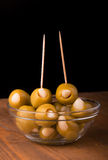 Green garlic stuffed olives in a glass bowl on wooden table Stock Image