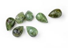 Green Garnet Teardrops. Seven green garnet teardrop-shaped gemstones, isolated on white background Stock Photo