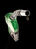 Green gas nozzle with one last drop. Of fossil fuel on black Stock Photography
