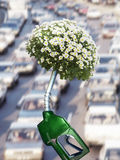 Green gas pump with blooming plant at end of nozzle and traffic in background Royalty Free Stock Photo