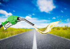 Green gas pump nozzle with oil splash on journey road Royalty Free Stock Photography