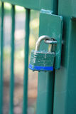 Green Gate and Blue Bottomed Lock. Vertical closeup of a green painted metal gate with a lock through the hasp Royalty Free Stock Photos