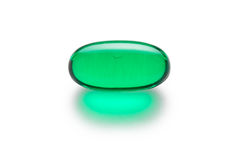Green Gelatin Capsule  on White. Green gelatin capsule or pill  on a white background.  Medically themed studio macro with backlighting for extra pop Royalty Free Stock Photo