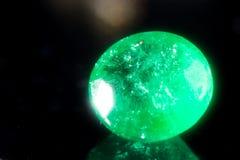 Green gem on a black background. Stock Images