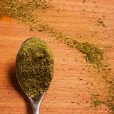 Green Georgian seasoning spicy taste on a metal spoon. On a wooden background Royalty Free Stock Images