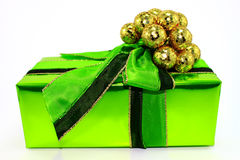 Green Gift. Shiny green Christmas gift with glittery gold balls and bow Royalty Free Stock Images