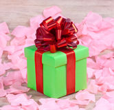 The green gift box. The green gift with a red ribbon on the rose petals stock photo
