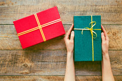 Green gift box in girl hands on old wooden table Royalty Free Stock Photos
