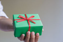 A green gift box in a hand Stock Images
