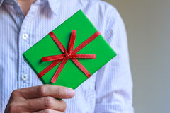 A green gift box in a hand Royalty Free Stock Image