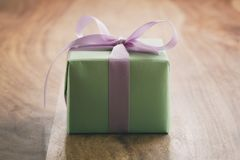 Green gift box with purple ribbon bow on old wood table with copy space Royalty Free Stock Photo