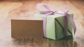 Green gift box with purple ribbon bow on old wood table with greeting card Stock Images