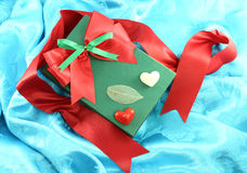 Green gift box with red ribbon. On blue satin Royalty Free Stock Image